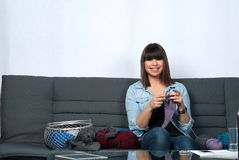 Young woman knits on the couch Stock Photography