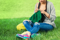 Young woman knits a green sweater Stock Photography