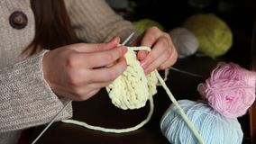 Young woman knits with needles and colored yarn stock footage