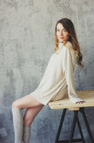 Young woman in knitted cardigan and warm socks wake up in the morning in cozy scandinavian bedroom and sitting on bed with white b Royalty Free Stock Photography