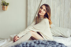 Young woman in knitted cardigan and warm socks wake up in the morning in cozy scandinavian bedroom and sitting on bed with white b Royalty Free Stock Images