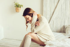Young woman in knitted cardigan and warm socks wake up in the morning in cozy scandinavian bedroom and sitting on bed with white b Royalty Free Stock Photo