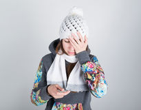 Young woman in a knitted hat and scarf, holding hands in the thermometer. she seems sick, holding his head Royalty Free Stock Photo