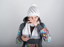 Young woman in a knitted hat and scarf, holding hands in the thermometer. she seems sick, scratching your nose, wipe the Royalty Free Stock Photo