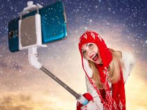 A young woman in a knitted hat scarf and mittens takes pictures of herself on the phone Stock Photos