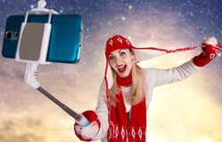 A young woman in a knitted hat scarf and mittens takes pictures of herself on the phone Royalty Free Stock Images