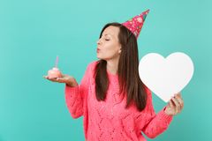 Young woman in knitted pink sweater birthday hat with closed eyes blowing out candle on cake hold white heart with copy. Space isolated on blue background stock photos
