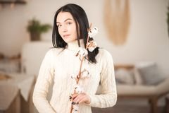 Young woman in knitted white dress sweater with a branch of cotton close-up. Girl in vintage romantic interior stock photo