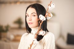 Young woman in knitted white dress sweater with a branch of cotton close-up. Girl in vintage romantic interior royalty free stock photos
