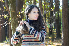 Young woman in knitted woolly sweater making braid. Young woman in knitted woolly sweater is making braid Royalty Free Stock Photography