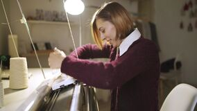Young woman knitting fabric on loom machine in textile workshop stock footage