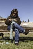 Young woman knitting a scarf. Young knitting in a park Royalty Free Stock Photography