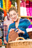 Young woman in knitting shop with circular needle. Young woman or saleswoman in knitting shop showing or explaining how to knit with circular needle Stock Images