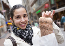 Young woman with Kurtos Kalacs in Hungary. An young woman with chimney cake (Kurtos Kalacs) at a main steet in Budapest, Hungary Stock Image
