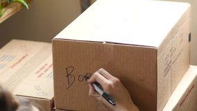 Young adult writing on a moving box. Young woman labels a moving box stock video