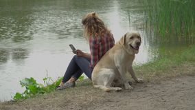 Young woman and labrador is sitting back to back stock video footage