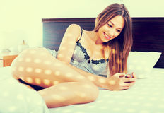Young woman in lace lingerie lying in bed with mobile phone in h Stock Photography