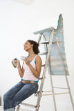 Young woman on ladder with mug taking break from hanging wallpaper, side view. Young women on ladder with mug taking break from hanging wallpaper, side view Stock Images