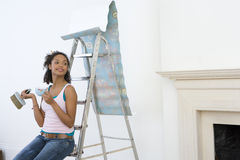 Young woman on ladder with mug taking break from hanging wallpaper, smiling. Young women on ladder with mug taking break from hanging wallpaper, smiling Stock Image