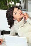 Young woman laid on a sofa with laptop Stock Image
