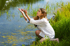 Young woman on the lake. Royalty Free Stock Image