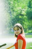Young woman by the lake. A view of a young woman wearing a red top by the lake with spray from a water fountain and green foliage in the background Royalty Free Stock Image