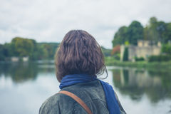 Young woman by lake in formal garden Stock Photo