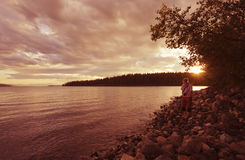 Young woman on lakeshore enjoying sunset Stock Photography