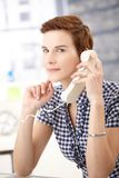 Young woman on landline call. Portrait of young woman concentrating on landline phone call, smiling royalty free stock photography