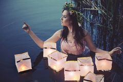 Young woman with lanterns. Young water nymph with lanterns Royalty Free Stock Photos