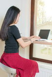 Young woman by lap top. Young asian woman by lap top Royalty Free Stock Photography