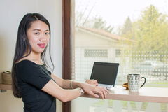 Young woman by lap top. Young asian woman by lap top Royalty Free Stock Images