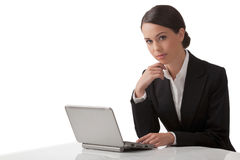The young woman with laptop. The young serious woman thoughtfully sits at a table with a laptop Royalty Free Stock Image