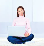 Young woman with laptop. Pretty young woman with laptop on carpet at home stock image