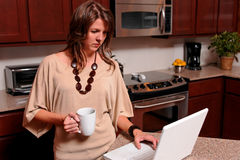 Young woman on laptop. Woman in her 30's standing in the kitchen with coffee and laptop computer stock photo