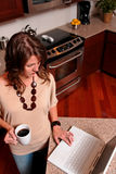 Young woman on laptop. Woman in her 30's standing in the kitchen with coffee and laptop computer royalty free stock photo