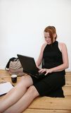 Young woman with laptop. A young woman with a laptop typing on the floor Stock Image