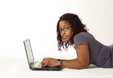 Young woman with laptop. Studio portrait of an African American young woman lying on the floor while working with her laptop and staring. Image isolated on white Stock Photo