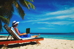 Young woman with laptop on beach Royalty Free Stock Photos