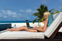 Young woman with laptop at the beach Royalty Free Stock Photos