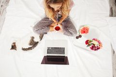 Young woman with laptop in the bed Royalty Free Stock Image