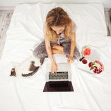 Young woman with laptop in the bed Royalty Free Stock Photos