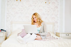 Young woman with laptop on bed Stock Photos