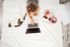 Young woman with laptop in the bed Stock Images