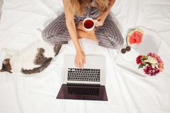 Young woman with laptop in the bed Stock Photos