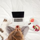 Young woman with laptop in the bed Stock Photo