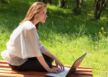 Young woman with laptop on a bench Stock Photo