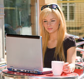 Young woman with a laptop at a cafe Royalty Free Stock Images