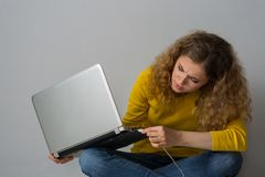 Young woman with laptop can not insert a wire from the mouse int Royalty Free Stock Images