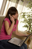 Young woman with laptop and Cell phone Royalty Free Stock Image